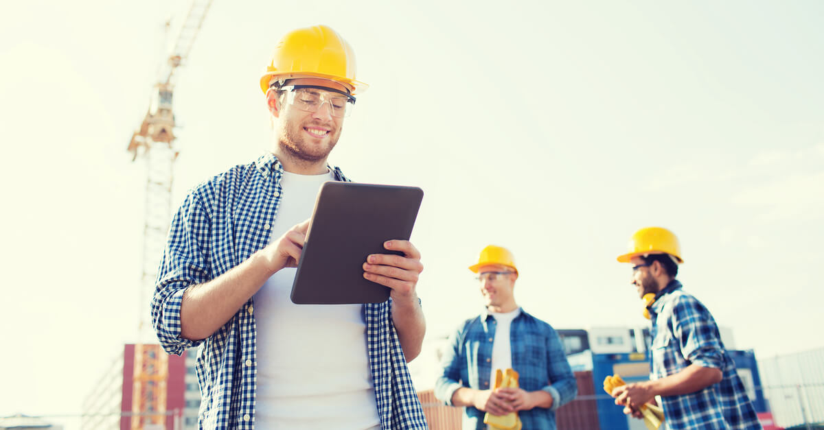 construction workers looking at tablet on site