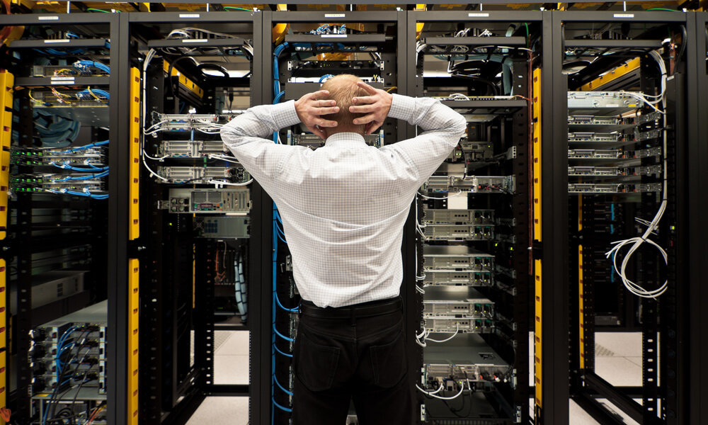 Man standing in data center looking concerned