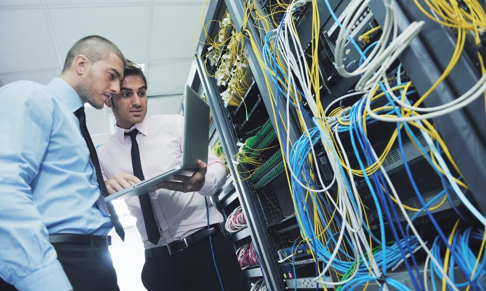 two business people examining a server and assessing IT network