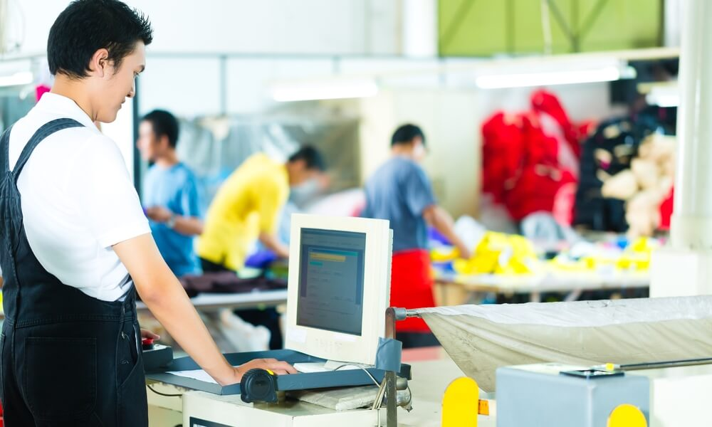 Asian man using computer on manufacturing floor
