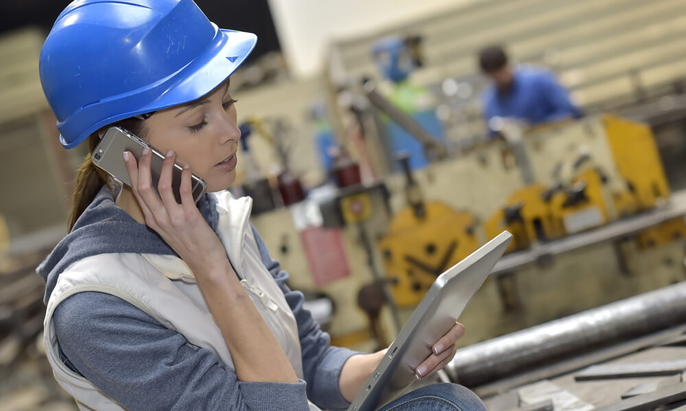 woman on manufacturing floor looking at tablet and talking on phone