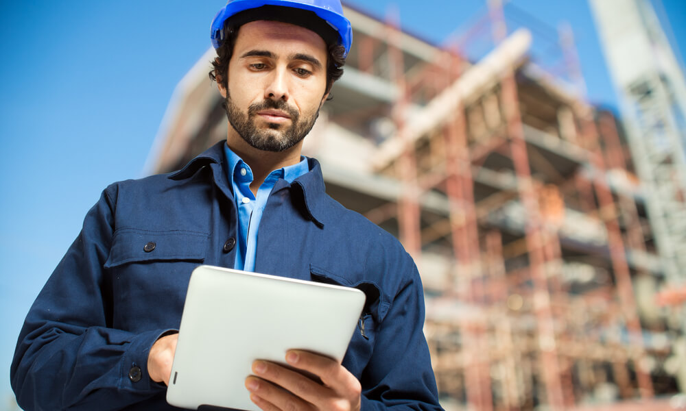 construction worker holding tablet on construction site