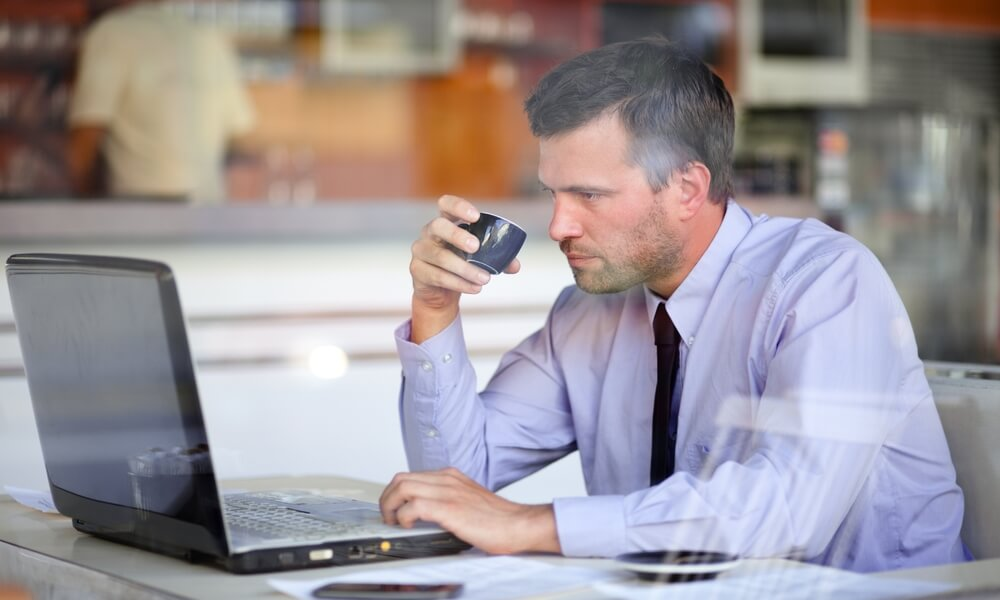 businessman at a remote office in a coffee shop working on computer and sipping espresso