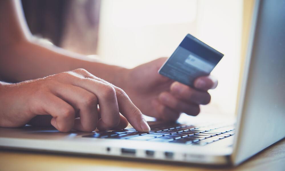 online shopper entering credit card information into laptop
