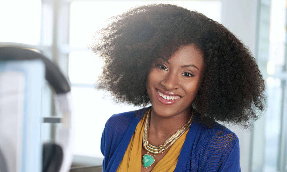 smiling African American female business owner with a headset over her computer