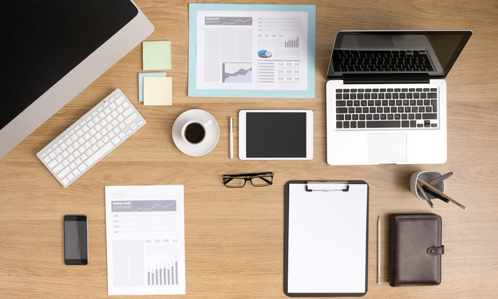 An organized office space with laptop, coffee, glasses, pencil case, and other supplies arranged neatly on a desk.