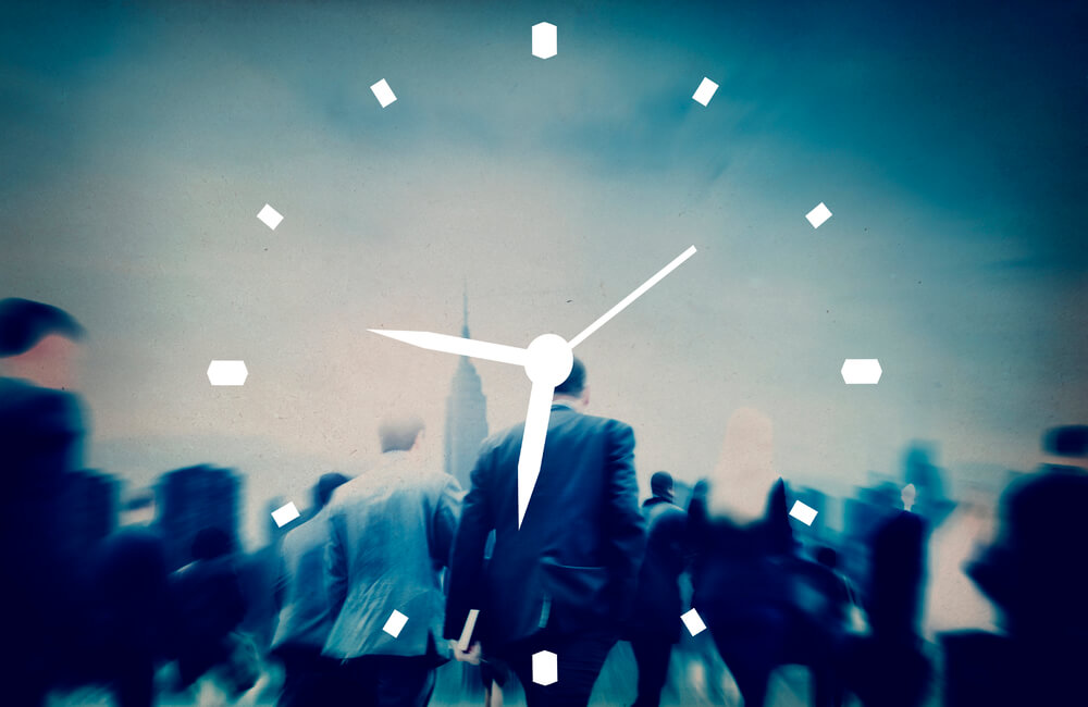 image of clock face imposed over a crowd of rushing businessmen.