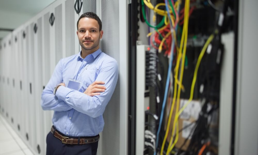 Man in colocation center next to a server rack.